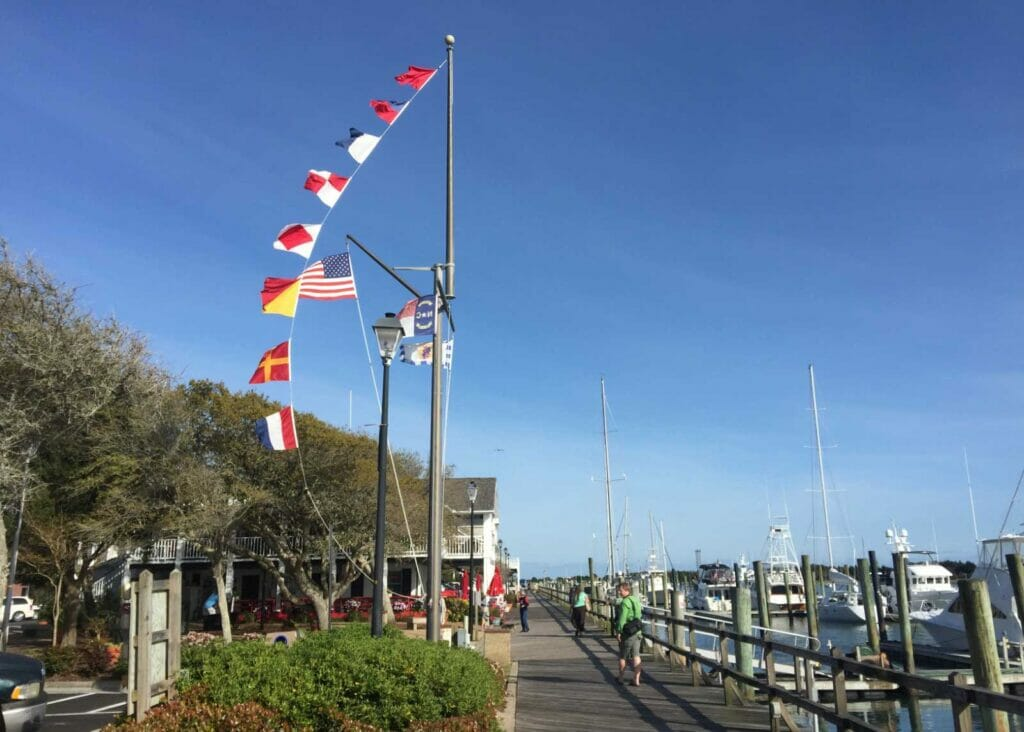 people walking on Beaufort Hotel Docks with boats on the left side and a flagpole with different flags on the left